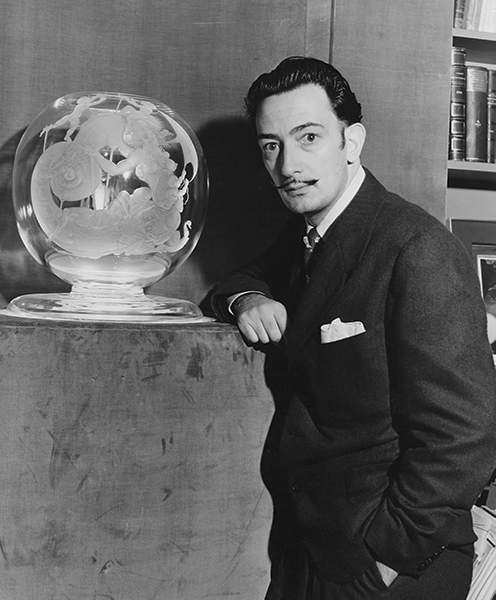 Salvador Dali poses with his piece from the 27 Artists in Crystal series